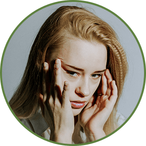 woman rubbing her temples - Treating Migraines - Benefit of Keto Diet